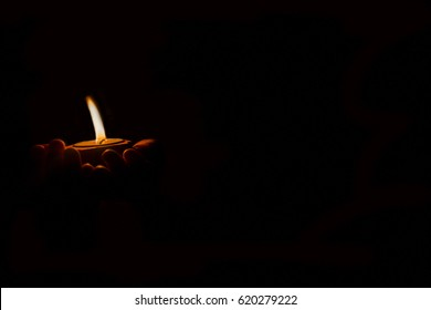 a childs hold a candle in hands,focus on candle isolated on dark background