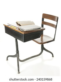 A child's old school desk with books and a pencil on top.  On a white background.