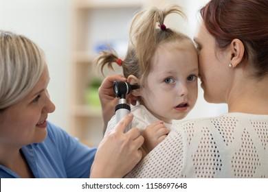 Child's otolaryngologist doing ear examination of kid girl. Mother holds daughter in her hands.