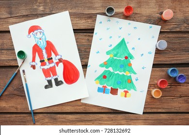 Child's paintings of Christmas tree with gifts and Santa Claus on wooden background