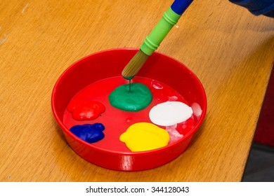 Child's paints in red container on wooden table