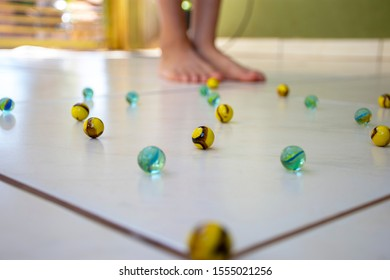 Child's play - Boy playing with colorful glass marbles