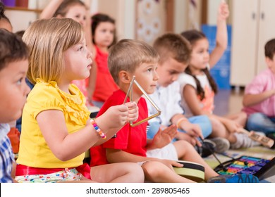 Childs playing musical instruments in classroom.