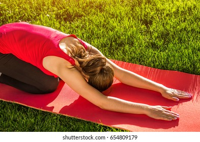 Child's pose. Practicing yoga in the park