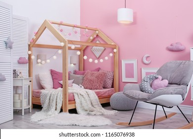 Child's room interior with comfortable bed and garland