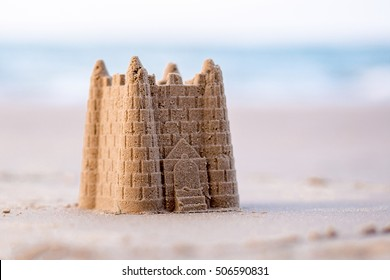 A Childs sand castle waiting for the  ocean tide to come in to reclaim it