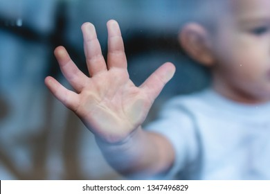 The child's small hand is pressed against the window glass with reflection. The concept of loneliness of children and waiting for kindness. Orphanage and orphans