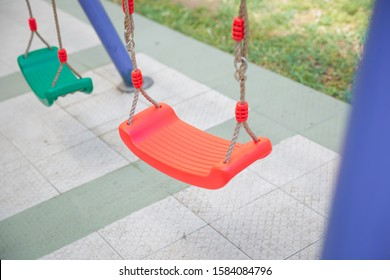 Childs swing in a park .Plastic and Empty red and green chain swings in children playground. chain swings hanging in garden