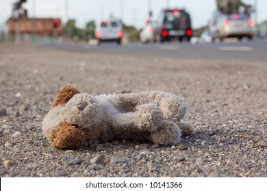 A child's teddy bear abandoned on the side of a busy road.