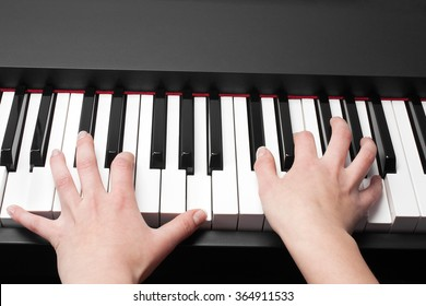 child's two hands playing the piano
