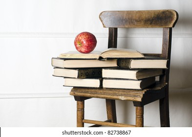 Kindervintage-Schulstuhl für alte Bücher und Apfel. Bildungskonzept.