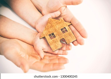 child's and woman's hands holds wooden flat house on the white background