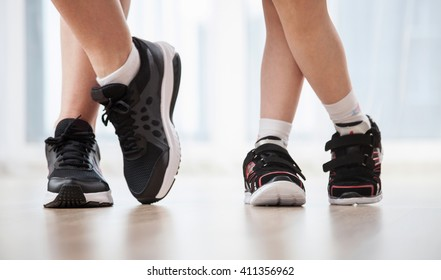 Child's and woman's legs in sports shoes, closeup shot