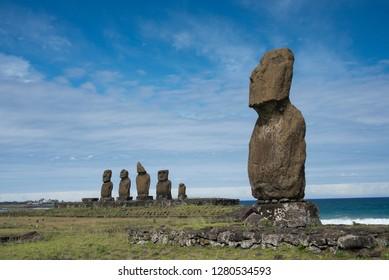 Chile, Easter Island aka Rapa Nui, Hanga Roa. Rapa Nui National Park. Ahu Tahai, a lone well weathered standing moai along the coast with Ahu Vai Uri in the distance with five moai.
