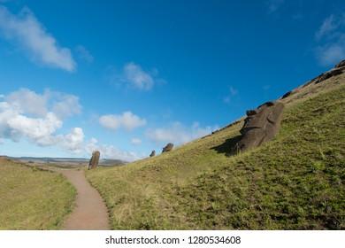 Chile, Easter Island aka Rapa Nui. Rapa Nui National Park, historic site of Rano Raraku 'the quarry'. Volcanic hillside where moai were carved. Stone moai with park walkways.
