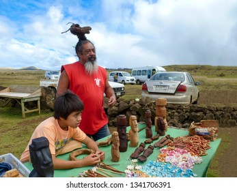Chile, Easter Island, February 15, 2013: Souvenir shop, figurines of statues, handmade decorations and tableware for sale to tourists.Moai descendants man and boy sell items at a flea market. Rapa Nui