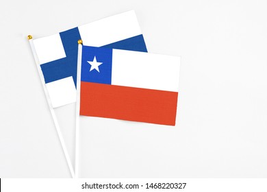 Chile and Finland stick flags on white background. High quality fabric, miniature national flag. Peaceful global concept.White floor for copy space.