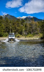 Chile, March 2017: A Land Rover Defender driving through a river in Patagonia.