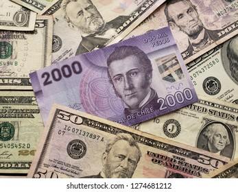chilean banknote of 2000 pesos and american dollars bills
