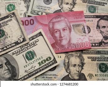chilean banknote of 5000 pesos and american dollars bills