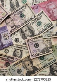 chilean banknotes and american dollar bills in different denominations unorganized