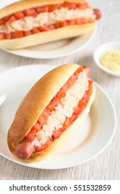 Chilean Completo Clasico (classical) or Aleman (German) traditional hot dog sandwiches with tomato and sauerkraut, photographed with natural light (Selective Focus, Focus one third into first hotdog)