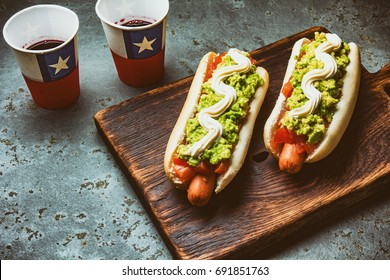 Chilean Completo Italiano. Hot dog sandwiches with tomato, avocado and mayonnaise served on wooden board with drink in paper cup . Top view. Independence Day concept.