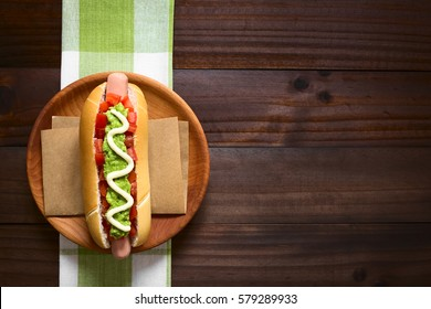 Chilean Completo Italiano (Italian) traditional hot dog sandwich, made with tomato, avocado and mayonnaise, photographed overhead on dark wood with natural light (Selective Focus on the hot dog)