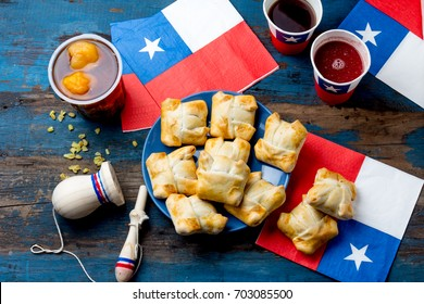 Chilean independence day concept. fiestas patrias. Chilean typical dish and drink on independence day party, Mini empanadas, mote con huesillo, wine with toasted flour chicha and tipical play emboque.