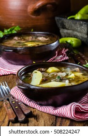 Chilean meat soup ajiaco. Latin American food. Ajiaco - traditional chilean soup with grilled meat, onion and potato served in clay plate from pomaire Chile