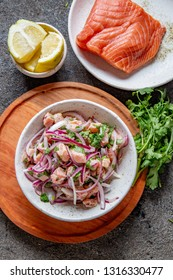 CHILEAN SALMON SEVICHE. Fresh raw salmon marinaded with purple onion, coriander in lemon juice. Ceviche and ingredientes on gray background. Top view