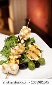 Chilean Sea Bass Kebab on a bed of arugula with lemon and olives