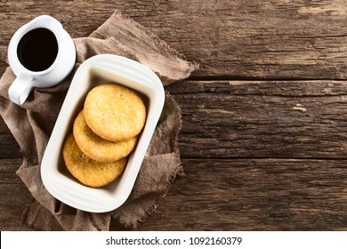 Chilean Sopaipilla nortena (made with pumpkin in the dough) deep-fried pastry with sweet chancaca raw cane sugar sauce on the side, a popular snack in autumn and winter, photographed overhead on wood