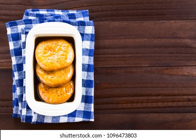 Chilean Sopaipilla pasada deep-fried pastry covered in chancaca cane sugar sauce, a popular snack in autumn and winter, photographed overhead on dark wood