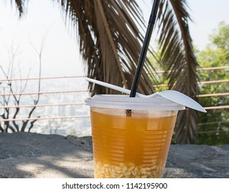Chilean traditional refreshing drink Mote con huesillos (peach compote with wheat). Street food in Chile. Against the background of palm tree.