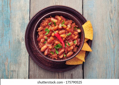 Chili Con Carne in bowl with tortilla chips on wooden background