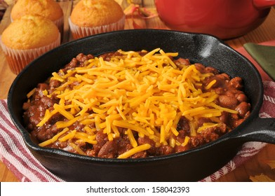 Chili con carne in a cast iron skillet topped with cheddar cheese