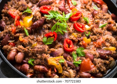 Chili con carne in a cast iron pan. Traditional mexican food. Close up.
