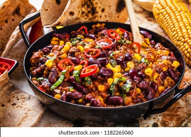 Chili con carne in a clay bowl on a concrete or stone rustic background- traditional dish of mexican cuisine