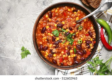 Chili con carne in a clay bowl on a concrete or stone rustic background- traditional dish of mexican cuisine.Top view.