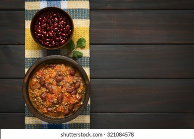 Chili con carne and dried kidney beans in bowls on kitchen towel, photographed overhead on dark wood with natural light