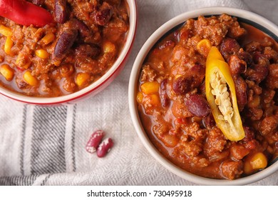 Chili con carne with fresh pepper in bowls on cloth