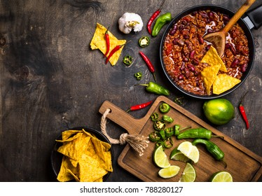 Chili con carne in frying pan on dark wooden background. Ingredients for making Chili con carne. Space for text. Top view. Chili with meat, nachos, lime, hot pepper. Mexican/Texas traditional dish