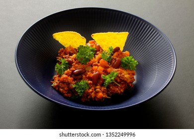 Chili con carne meal in a rustic bowl. Traditional dish of mexican cuisine with kidney beans, minced meat, parsley and tortilla chips