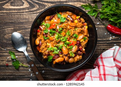 Chili con carne from meat, beans and vegetables on dark wooden table. Traditional mexican food. Top view.