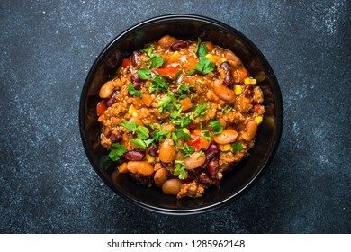 Chili con carne from meat, beans and vegetables on black stone table. Traditional mexican food. Top view.