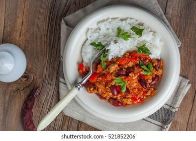 Chili con carne with paprika, tomatoes, onion, red bean and garlic in a clay bowl.
