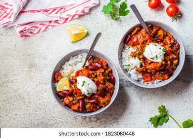 Chili con carne with rice in a gray bowl. Beef stew with beans in tomato sauce with sour cream and rice. Traditional Mexican food concept.