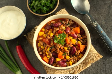 Chili con carne in a rustic bowl on a grey stone background- traditional dish of mexican cuisine