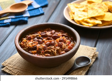 Chili con carne in rustic bowl with homemade tortilla chips in the back, photographed with natural light (Selective Focus, Focus one third into the chili)